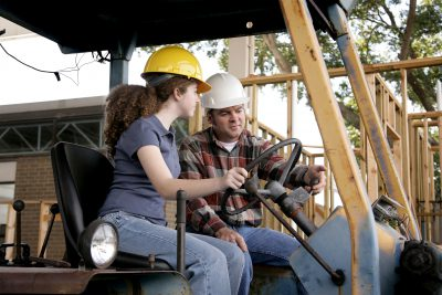 A construction foreman instructing a new worker on driving heavy equipment. Focus on the foreman