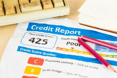 Poor credit score report on wrinkled paper with pen and keyboard