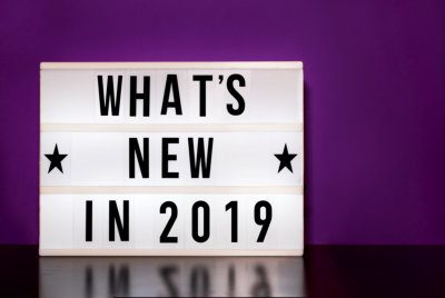whats new in 2019 sign - cinema style lettering on light box and purple background
